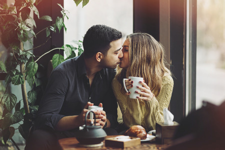 hugs and kisses: Couple in love drinking coffee and have fun in coffee shop. Love concepts. Vintage effect style picture