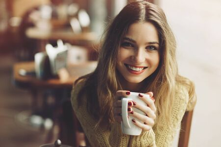 charming girl: charming girl drinking cappuccino and eating cheesecake in coffee shop
