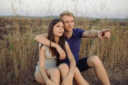 couple background: Young couple in love sitting on the grass in the field