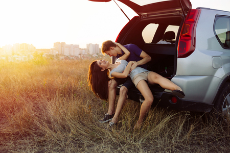 Young couple in love. Sitting in the trunk of an SUV