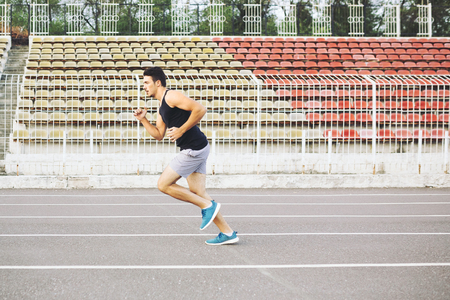Athletic man running on a racing track
