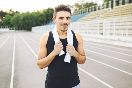 work out: Jogger resting after running. Man runner taking a break during training outdoors. Young Caucasian male fitness model after work out. Stock Photo