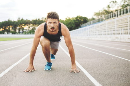 starting position: Male athlete on starting position at athletics running track