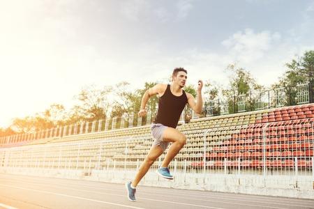Atletico uomo che corre su una pista da corsa