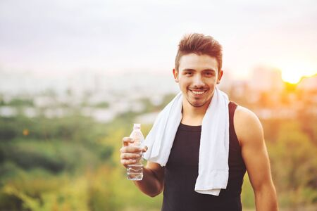 Young man drinking water on te city background Stock Photo