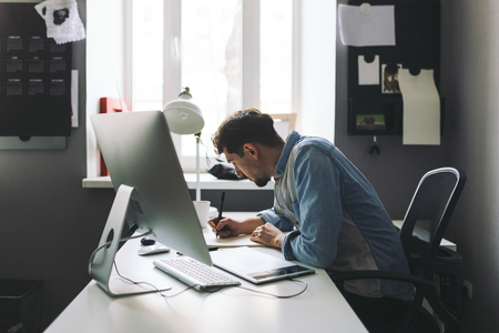 designer: Modern designer sitting in front of computer and working in office Stock Photo