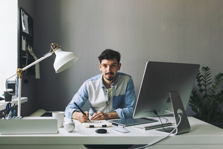 designer working: Modern designer sitting in front of computer and working in office Stock Photo