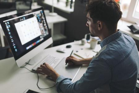 コンピューターの前に現代のデザイナー リビングやオフィスで働く