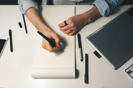 drawing pad: Designer at work in office. Man drawing in note pad Stock Photo