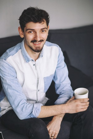 offiice: Handsome casual man sitting on couch having coffee at home in the offiice