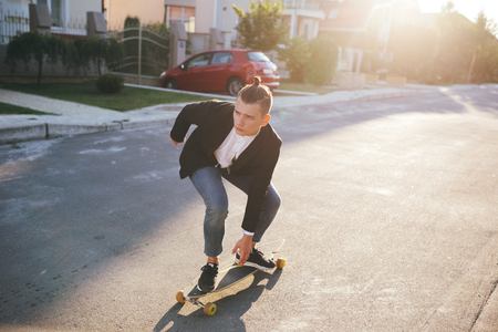 skater boy: Vintage image of a man with longboard going on road,hipster young teen boy, sunset lights,mans hairstyle, mans fashion, urban street style