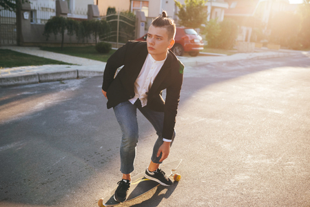 handsome men: Vintage image of a man with longboard going on road,hipster young teen boy, sunset lights,mans hairstyle, mans fashion, urban street style