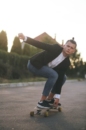 Vintage image of a man with longboard going on road,hipster young teen boy, sunset lights,mans hairstyle, mans fashion, urban street style
