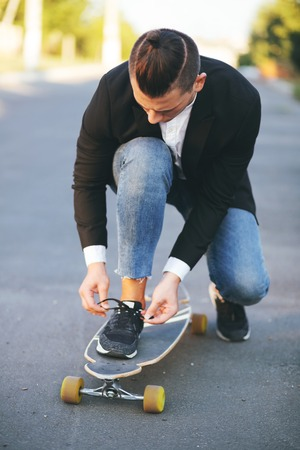 fashion boy: Vintage image of a man with longboard going on road,hipster young teen boy, sunset lights,mans hairstyle, mans fashion, urban street style