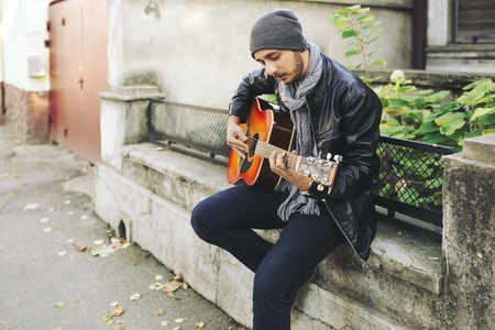 Portrait of young attractive street artist with his guitar Stock Photo