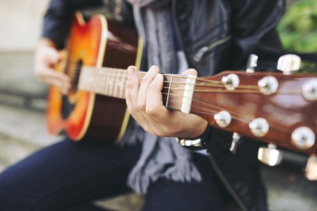 Young attractive street artist with his guitar. Guitar close-up Stock Photo