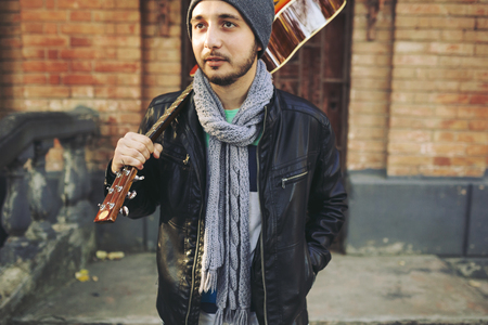 Young attractive street artist with his guitar. Walking in the street with acoustic guitar