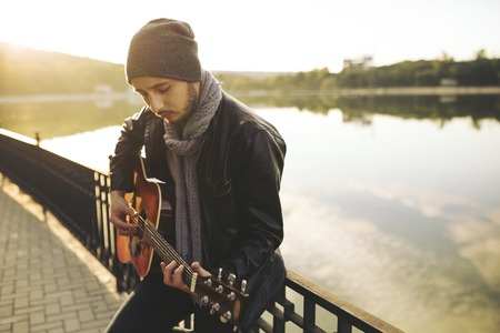 Portrait of young man playing on guitar at the lake