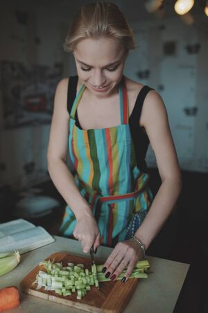 cutting vegetables: Young woman cutting vegetables in the kitchen Stock Photo