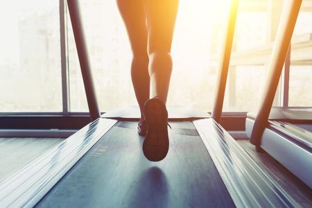 トレッドミルで実行されているフィットネス女の子。ジムで足の筋肉を持つ女性