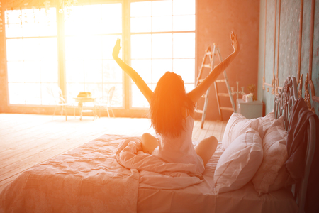 Woman stretching in bed after wake up, back view Stockfoto