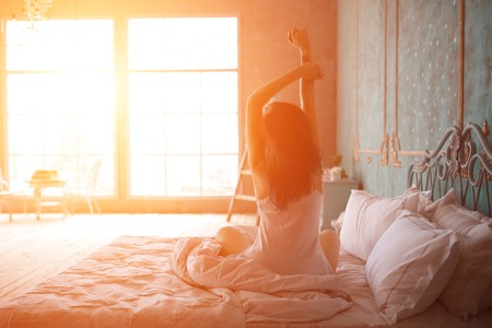 Woman stretching in bed after wake up, back view Archivio Fotografico