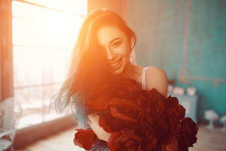 mujer con rosas: Imagen de mujer joven y hermosa con el ramo de rosas en su dormitorio