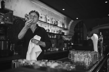 bartending: Barman at work in the pub rubs the glass. Black and white photo