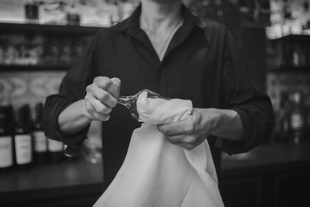 bartending: Barman at work in the pub rubs the glass. Black and white photo. Close up on hands