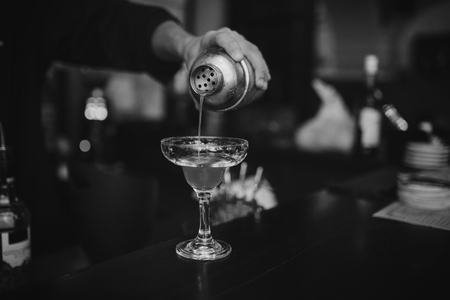 Barman at work in the pub making cocktails. Black and white photo