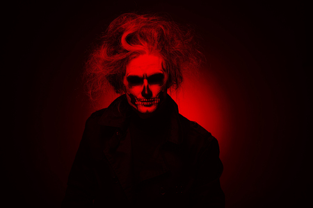 Portrait man with Halloween skull makeup. Halloween or horror theme. Red filter