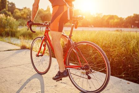Junger Mann sind Radfahren Rennrad durch den See im Park
