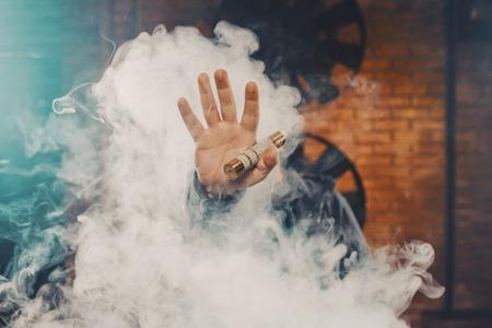 Vaping man wearing a hat, holding up a mod, obscured behind a cloud of vapor. Standard-Bild
