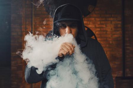 蒸気の雲の後ろに隠れて、帽子をかぶった Vaping 男。