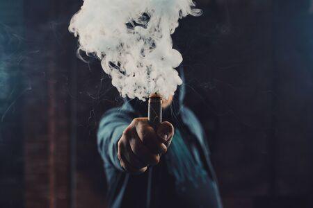 Vaping の男の帽子をかぶって蒸気の雲の後ろに隠されている mod を保持します。