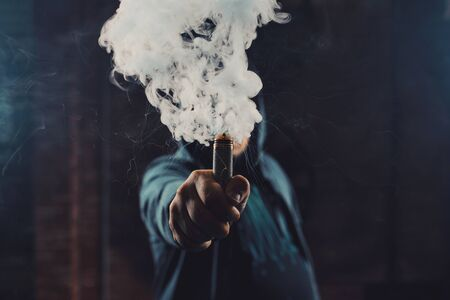 Vaping man wearing a hat, holding up a mod, obscured behind a cloud of vapor. Stock Photo
