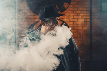 Vaping man wearing a hat, obscured behind a cloud of vapor.