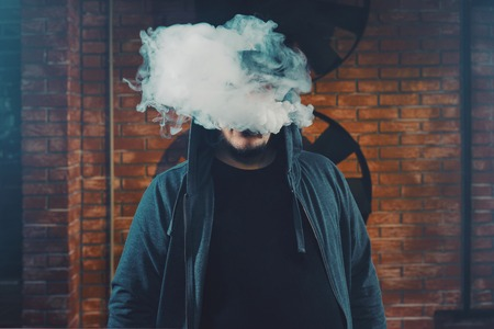 obscured: Vaping man wearing a hat, obscured behind a cloud of vapor.