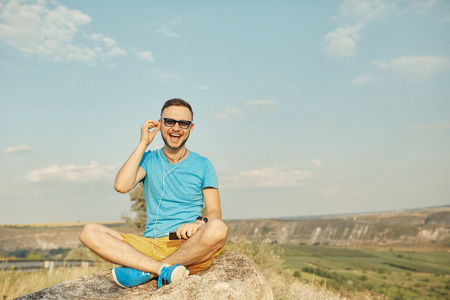 Young man wearing sunglasses smiling and listening to music while sitting on a stone