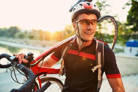 cycliste Jeune et énergique dans le parc. Homme tenant un vélo sur son épaule
