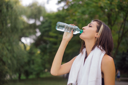 brightness: Smiling jogger woman drinks water from a bottle