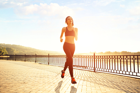 Woman running by the lake at sunset. Sport and lifestyle concept Stock Photo