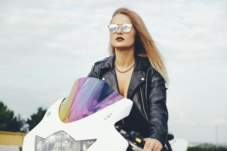 Biker girl in a leather clothes on a white motorcycle. Sexy young woman biker sitting on her motorcycle on a road. Adventure concept.