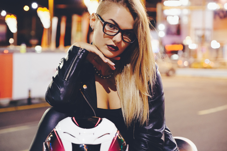 Biker girl in a leather clothes on a white motorcycle. Sexy young woman biker sitting on her motorcycle. Adventure concept. City night lights Stock Photo