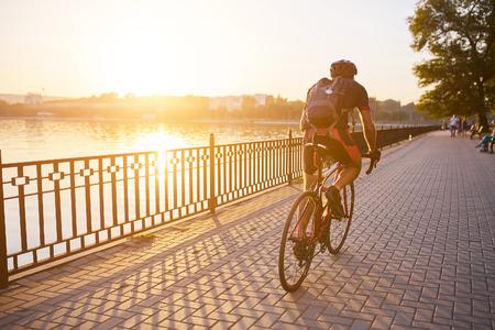 若い男が公園内の湖でロードバイクをサイクリングします。