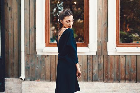 旧市街の通りを歩いて美しいブルネット若い女性。ファッションの概念 写真素材