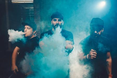벽돌 벽이있는 정통 방에서 세 남자가 점프. 전자 담배를 많이 피우며 담배를 피우다. 스톡 콘텐츠
