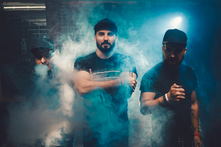 Three men vaping in an authentic room with brick walls. Vaping an electronic cigarette with a lot of smoke Foto de archivo