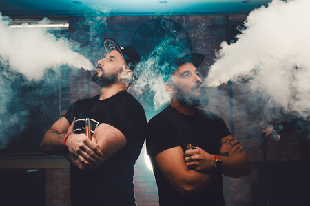 non violence: Two men vaping in an authentic room with brick walls. Vaping an electronic cigarette with a lot of smoke Stock Photo