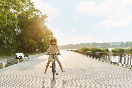 Outdoor fashion portrait of attractive young brunette in a hat on a bicycle.